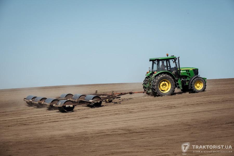 Трактор John Deere прикочує посіви