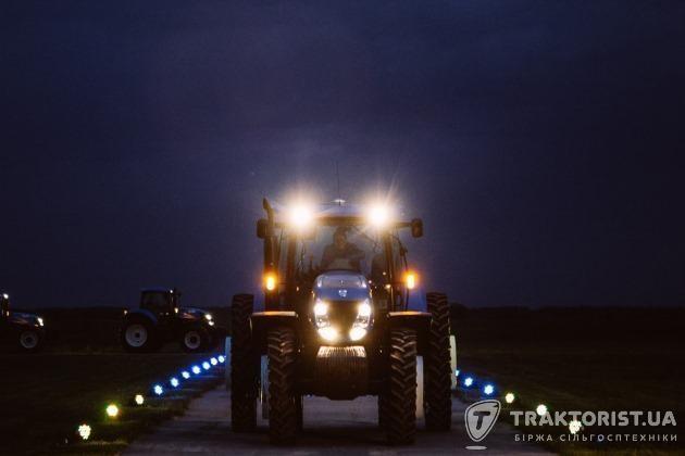 Трактори New Holland їдуть вночі