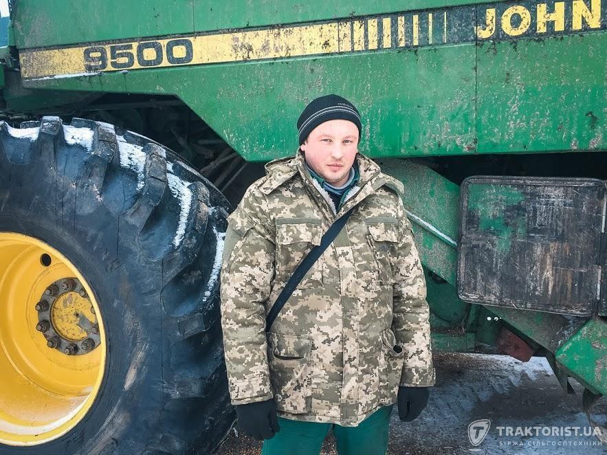 Комбайнер Олег Козаченко біля комбайна John Deere 9500