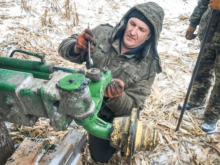 Комбайнер Олександр Мельник під час ремонту комбайна John Deere 9500