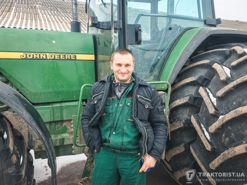 Тракторист Олександр Верещако біля трактора John Deere 8400